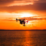 drone with remote control. Dark silhouette against colorfull sunset. Soft focus. Toned image